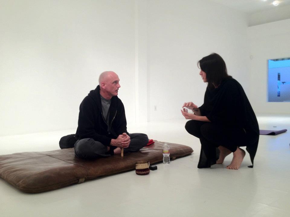Frank Uyttebroeck zittend op meditatiemat praat met vrouw