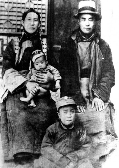 De veertiende Dalai Lama op schoot bij zijn moeder.