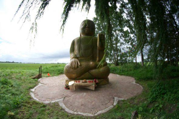 Het metershoge boeddhabeeld in het park van het centrum Gaden Chökor Ling